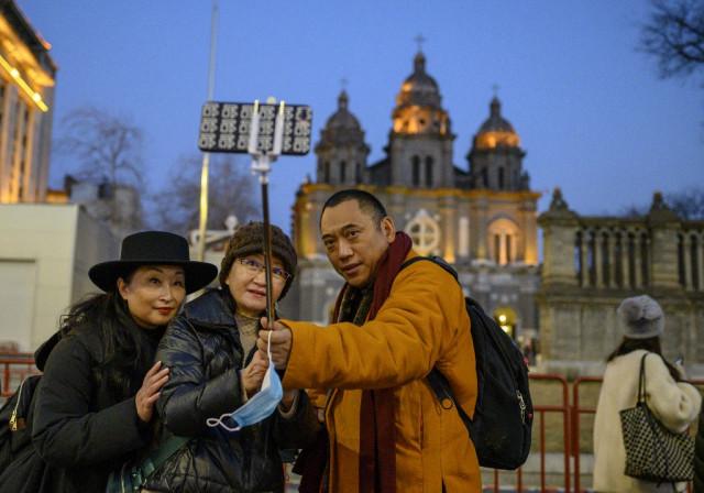 China hails its 'extraordinary' success curbing virus ahead of WHO probe